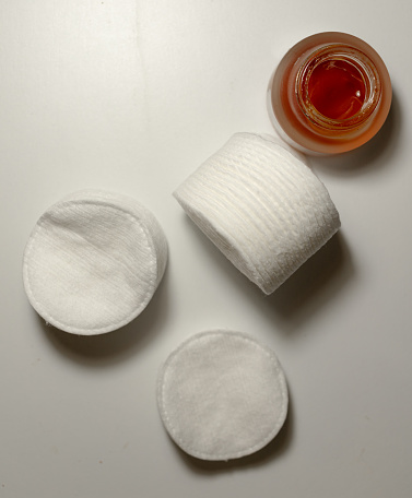 white face sponges are spread out on a white surface. there is container glass of red cream. maroon. cozy comfortable light