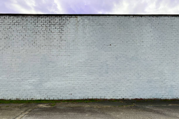 white faded stone brick factory warehouse wall alley stock photo