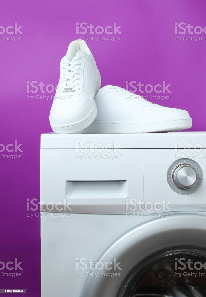 White fashion sneakers on the washing machine against the background...
