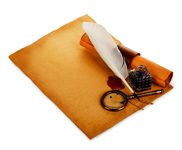 White feather, inkwell, loupe, ancient scroll with red wax seal. stock photo