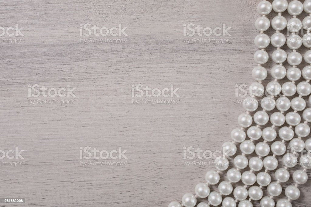 white female beads on white wooden background, female jewelery on a white wooden table stock photo