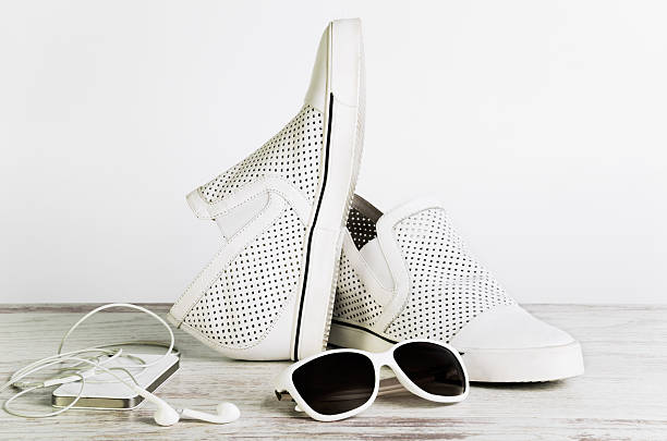 White female shoes, sun glasses and  smart phone with headphone – Foto
