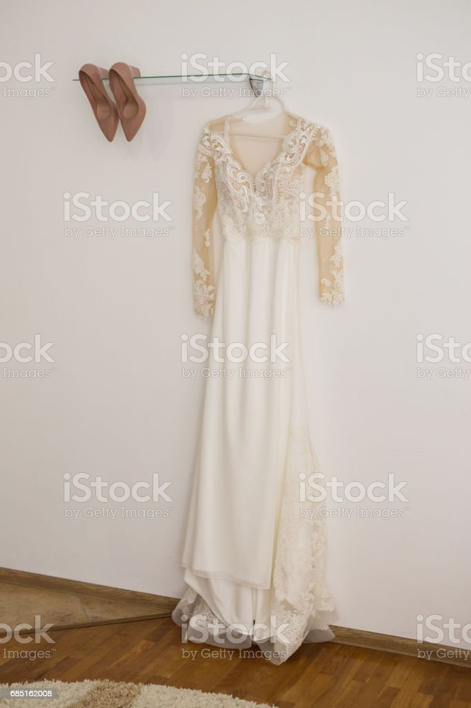 White female wedding dress hanging on a hanger. Women's shoes foto de stock royalty-free