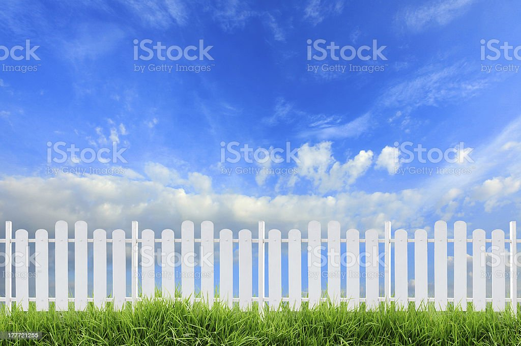 White fence on green grass and a slightly cloudy blue sky stock photo