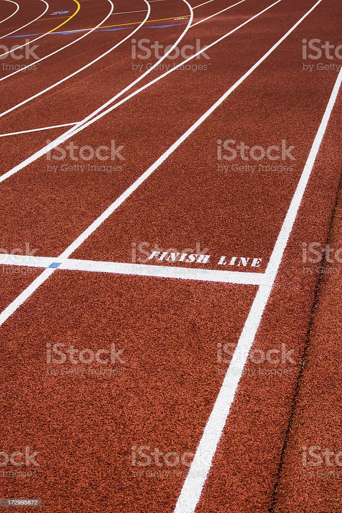 White finish line text and lane on red running track royalty-free stock photo