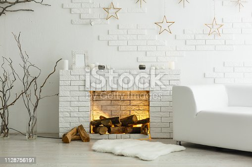 istock White fireplace in light room with Christmas decoration 1128756191