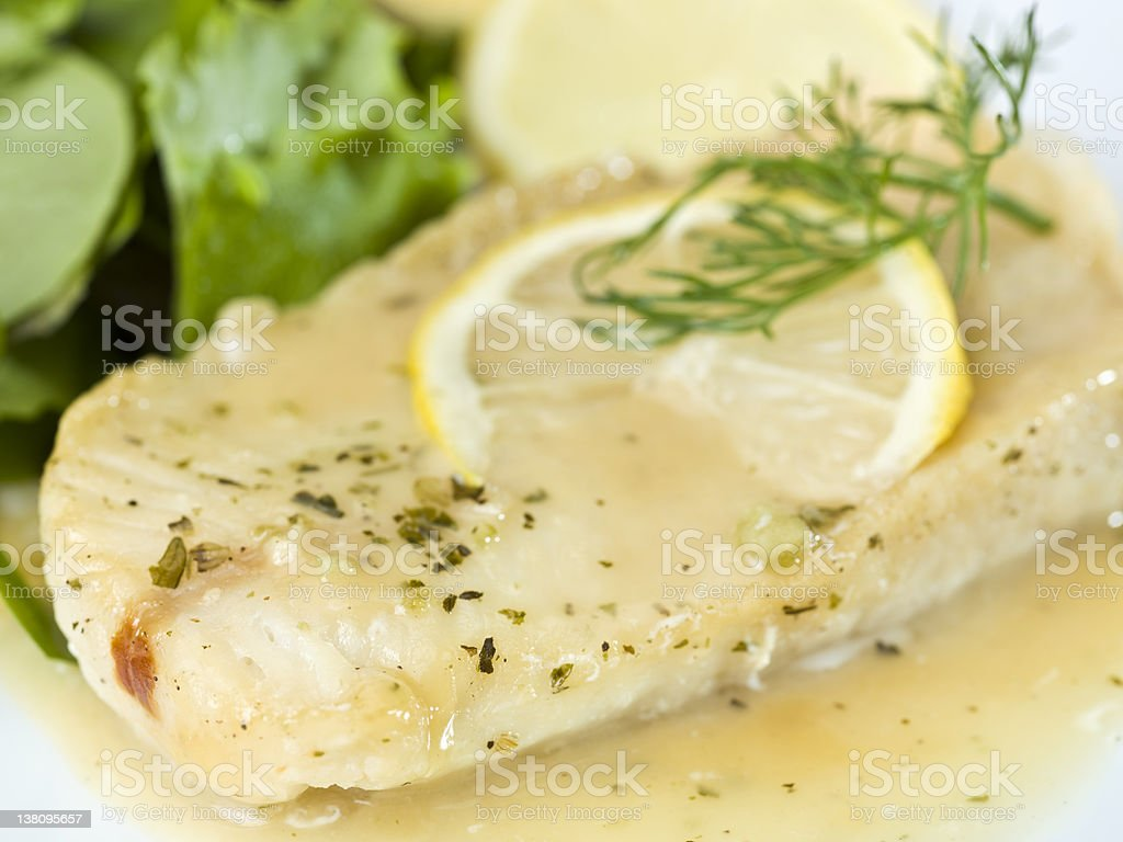 White Fish Fillet in lemon and herbs sauce stock photo