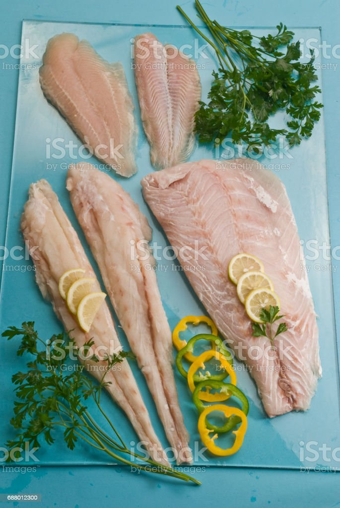 white fish fillets with parsley and peppers slices stock photo