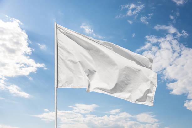 White flag against the blue sky stock photo