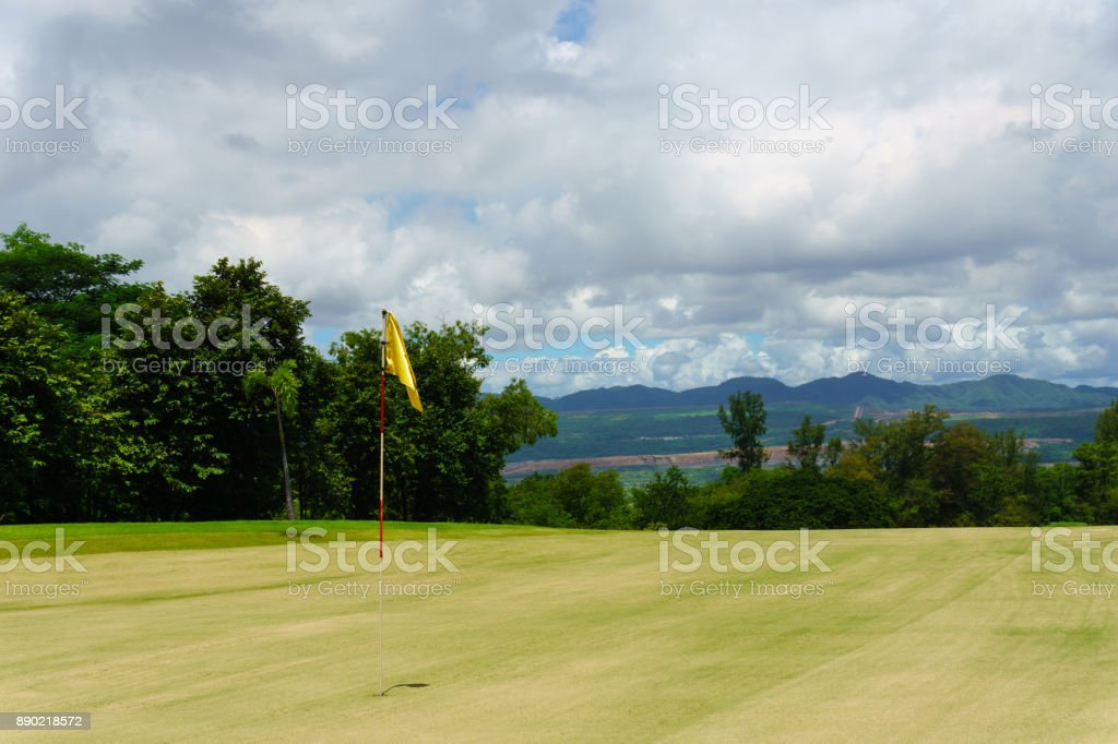 white flag on top soil green with view of forest ,mountain, blue sky with cloud. stock photo