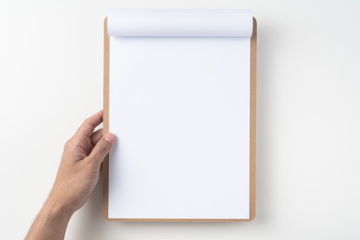 Design concept - top view of man hand hold white A4 flipped paper on brown clipboard isolated on white background for mockup. real photo, not 3D render