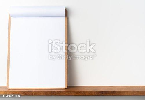 istock white flipped paper on clipboard on bookshelf 1148751004