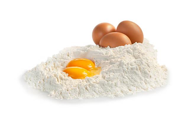 White flour and raw eggs on white background stock photo
