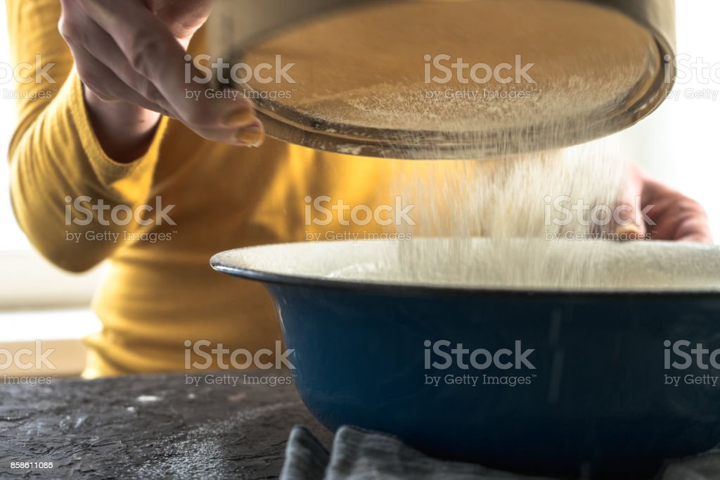 White flour is sieved in a large blue bowl stock photo