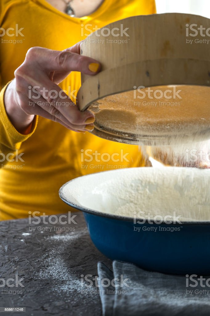 White flour is sieved into a large blue bowl with a free space stock photo