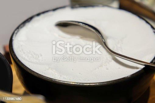 Close up white flour on a black bowl