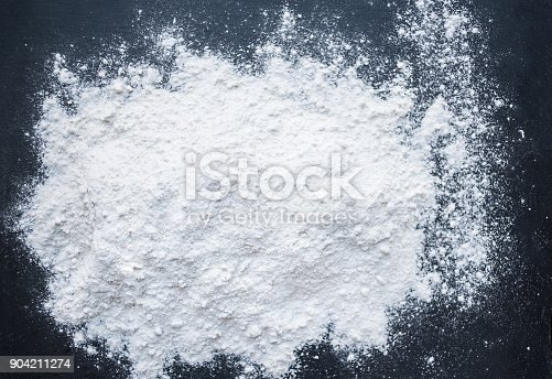istock White Flour powder on black background as dust splash clouds. Baking preparation, top view. Cooking recipe concept