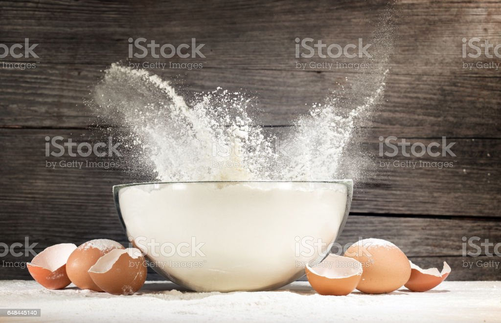 white flour splashing out of a glass bowl stock photo