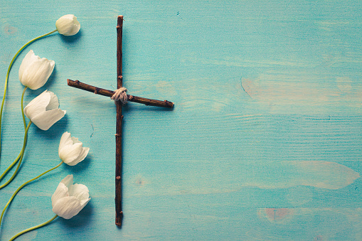border of white anemone flowers with wood cross on blue wood background with copy space