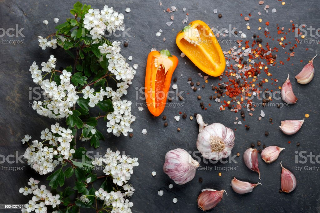 White  flower blossoms with pink garlic and Himalayan rock salt with colorful pepper and chilli royalty-free stock photo