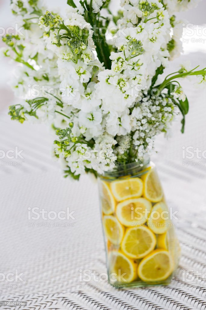 White flower bouquet in the vase which decorated with lemon slices for fresh air smelling stock photo