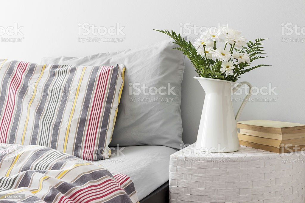 White flowers and books on a bedside table stock photo