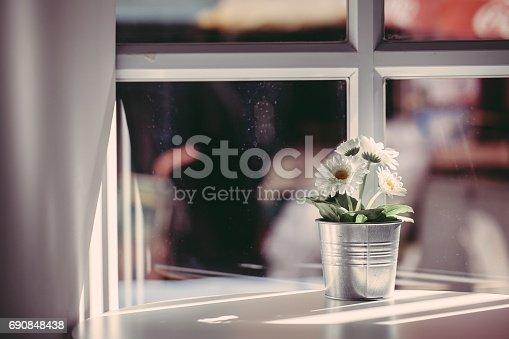 697868238 istock photo white flowers in a tin pot near the window 690848438