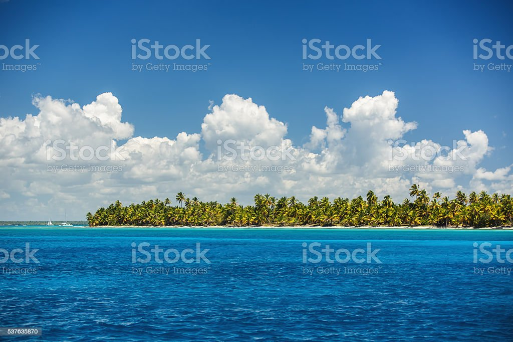 White fluffy clouds blue sky above a sea surface stock photo
