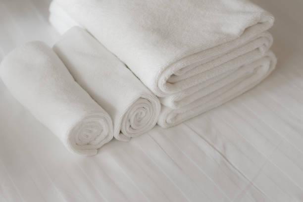 weiße flauschige Handtücher auf dem Bett im Hotelzimmer. Nahansicht – Foto