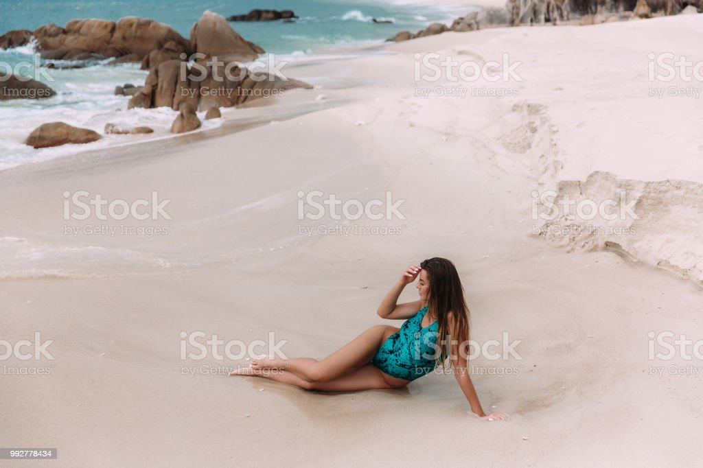 White foamy waves barely touch the long tanned legs of a young beauty who lies on the white sand of a paradise wild beach. The girl corrects her long hair with her hand and looks at the blue water stock photo