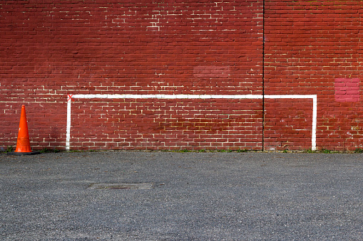 White football or soccer goalposts painted on red brick wall with foreground tarmac and with traffic cone to one side