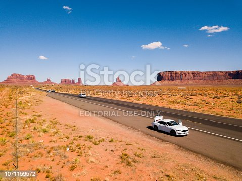 Monument Valley National Park, Utah, USA - July 30, 2018: White Ford Mustang parked by the side of the road at Monument Valley National Park with an amazing view on the infinite road through the desert.