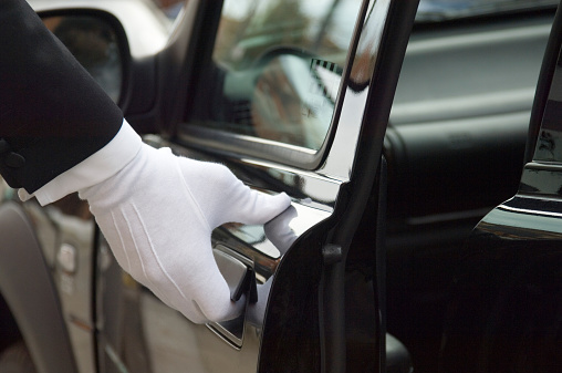 The white gloved hand of a uniformed doorman / chauffeur opening / closing a black car door.