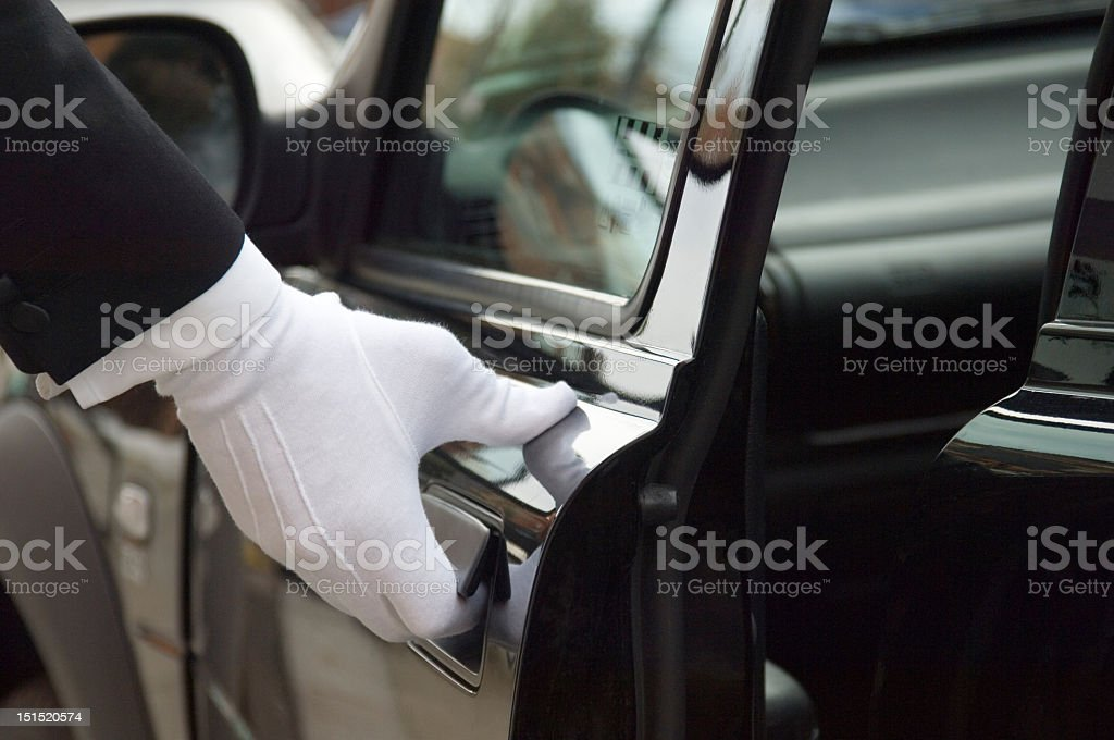 White formal gloved uniformed hand opening car door stock photo