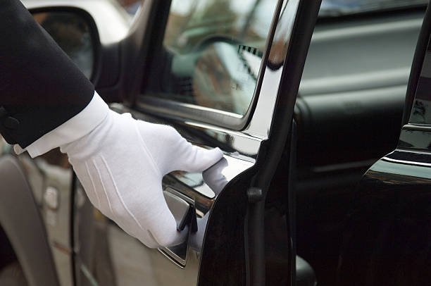 White formal gloved uniformed hand opening car door The white gloved hand of a uniformed doorman / chauffeur opening / closing a black car door. first class stock pictures, royalty-free photos & images