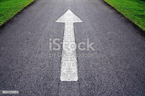 istock White forward arrow sign on grey asphalt road through the green grass field 855425554