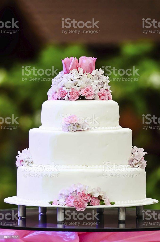 White four tiered wedding cake on table stock photo