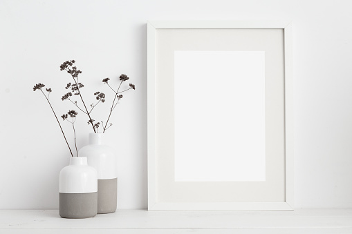 istock White frame and dry twigs in vase on book shelf or desk. White colors. 1067194410