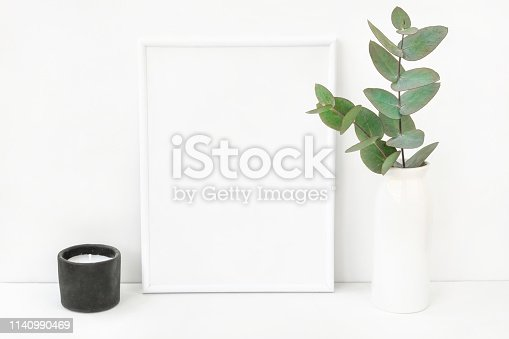 istock White frame mockup composition with branches of green silver dollar eucalyptus in ceramic vase black candle on table wall background. Copy space for text lettering artwork. Elegant minimalist 1140990469