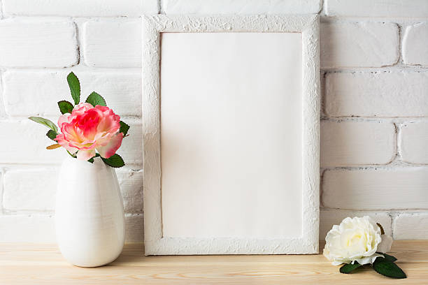 White frame mockup on brick wall with roses stock photo