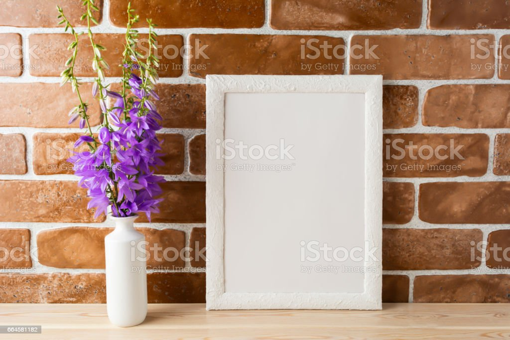 White frame mockup with campanula bouquet near exposed brick wall royalty-free stock photo