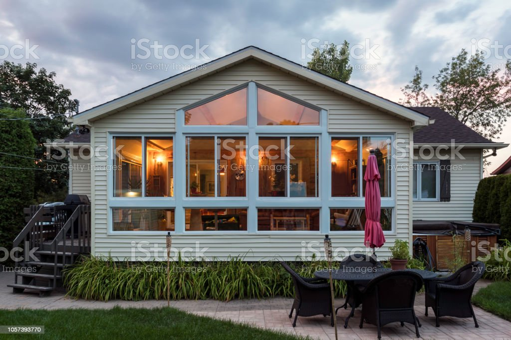 White framed glass conservatory attached to house at sunset, Quebec, canada stock photo