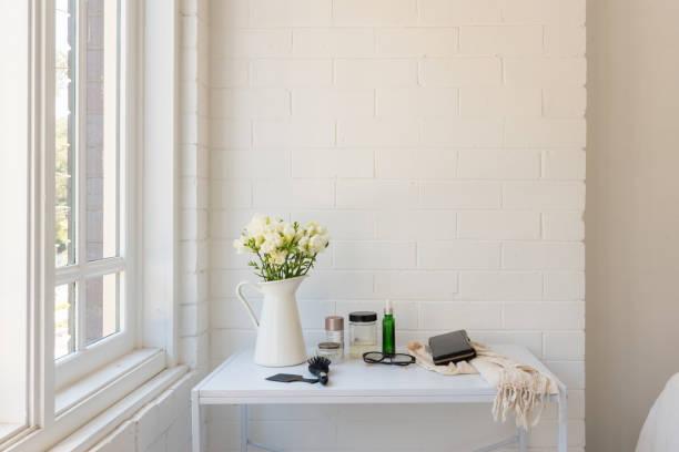 White freesias in jug on dressing table next to window stock photo