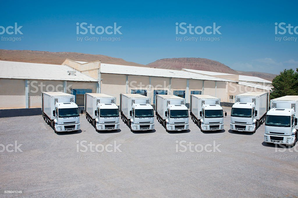 White Freight trucks trailers at logistics warehouse loading docks stock photo