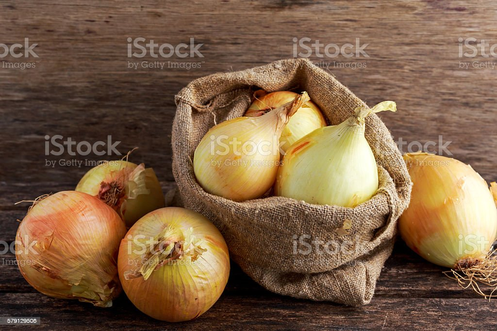 White freshly harvested onion in burlap bag on wooden old stock photo