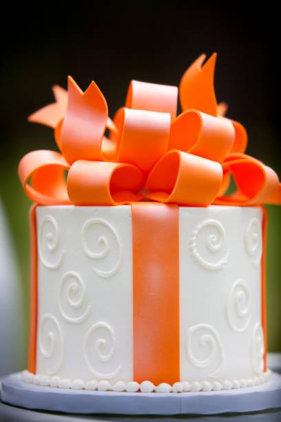 white mattiertes kuchen mit orange marzapan schleife - orange hochzeitstorten stock-fotos und bilder
