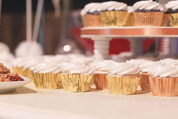 White Frosted Cupcakes Displayed on Tiered Cake Stand stock photo