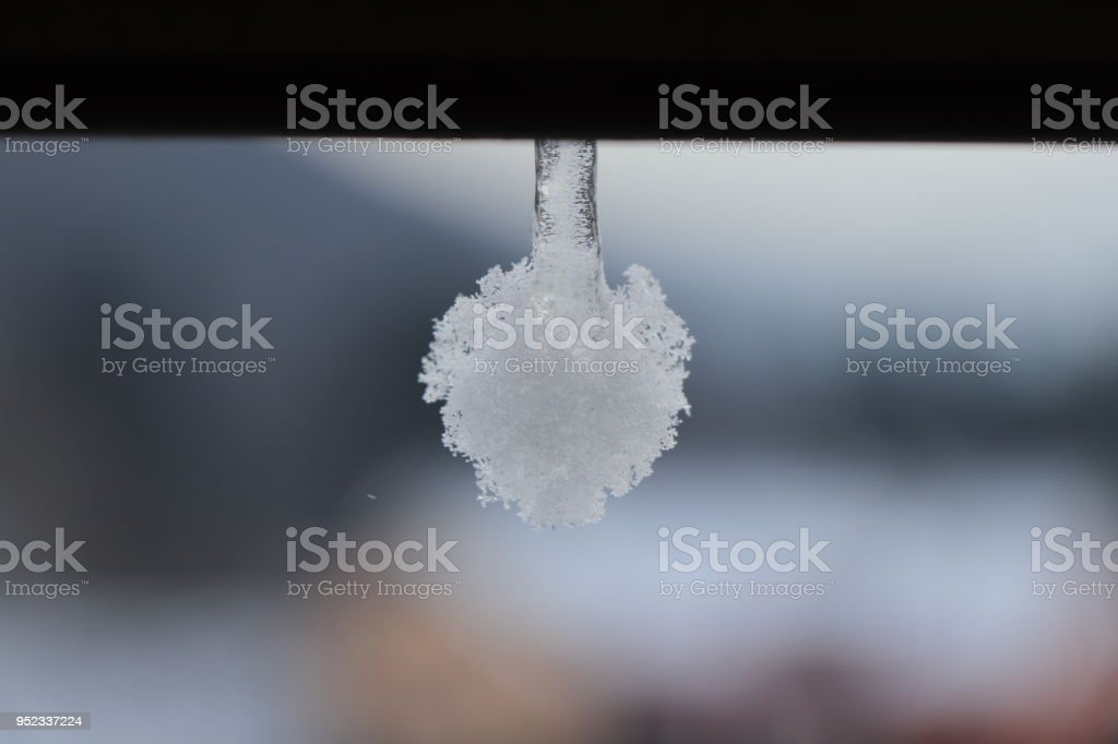 A  white frozen ball hanging on old gutter stock photo