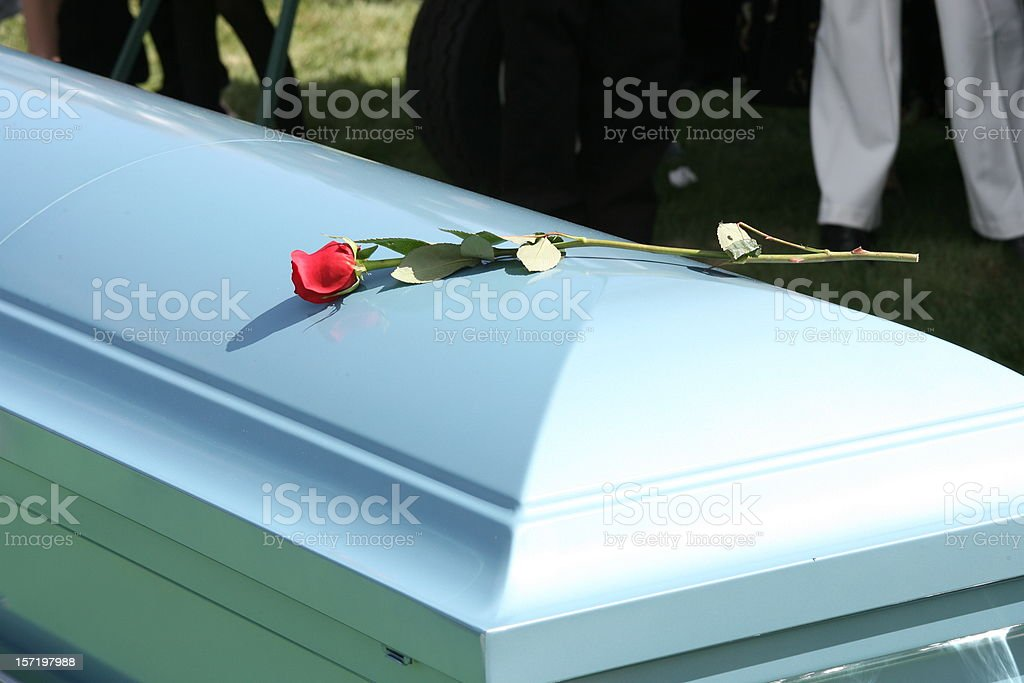 White funeral casket with a single red rode placed on top stock photo