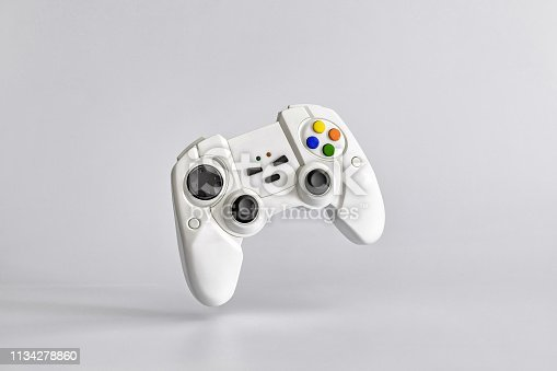 White gamepad on white uniform background. Minimalism. Copy space for text